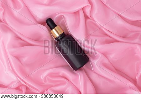 Matte Black Cosmetic Bottle With Dropper On A Background Of Wet Folds Of Pink Silk. Mockup Bottle Fo