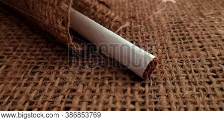 Single Cigarette On Brown Sack Mat Background, Pack Of Cigarettes, Close-up Of A Cigarette