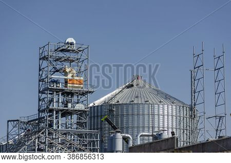 Construction Of A Modern Grain Terminal On A Blue Sky Background. Metal Cylindrical Silo And Support