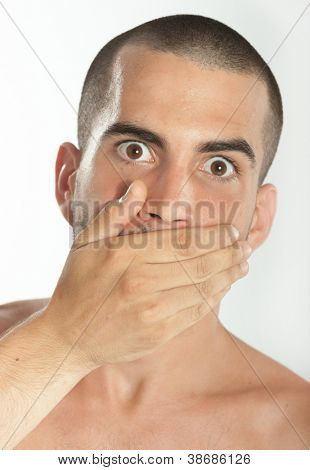 Young man covering his mouth with his hand