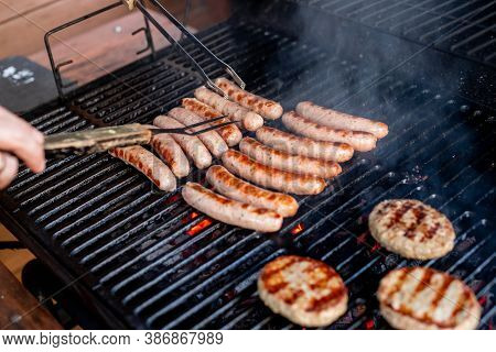 Man At A Barbecue Grill With Smoke.grilling Sausages On Barbecue Grill. Bbq Party.delicious German S