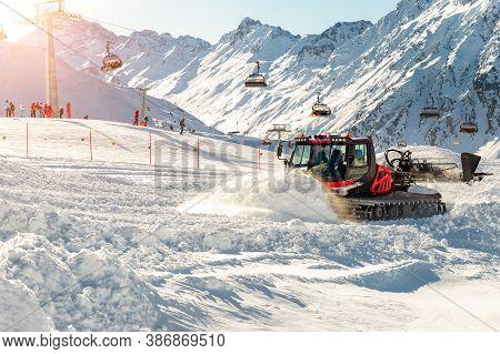 Red Modern Snowcat Ratrack With Snowplow Snow Grooming Machine Preparing Ski Slope Piste Hill At Alp