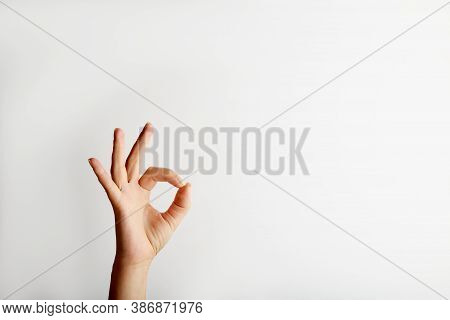 Female Hand Shows Okay Gesture From Down, On White Background With Free Space For Text