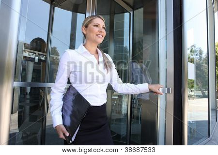 A pretty blonde business woman leaving the office building through glass doors