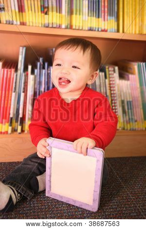 A young baby boy happily playing in the library