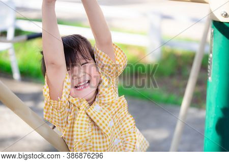 Happy Child Girl Is Playing, Climbing Or Hanging Up With A Gym In The Village Playground. Asian Chil