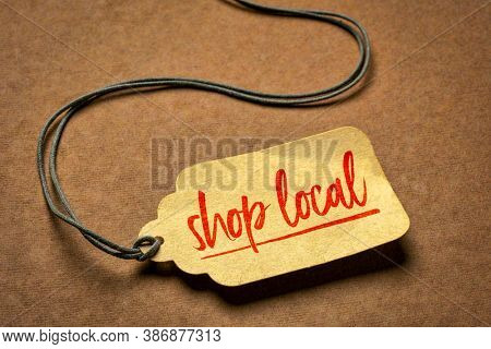 shop local  sign a paper price tag against brown paper background - business and shopping concept