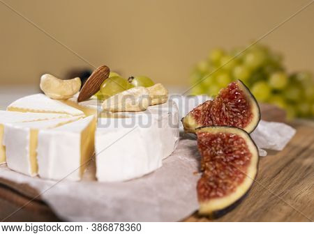 Camembert Cheese On Wooden Board, Branch Of Green Grapes , Slice Of Figs And Nuts.