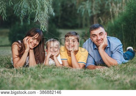 Beautiful Happy Caucasian Family Of Four People In Park On Summer Day. Mother And Father Hugging Two