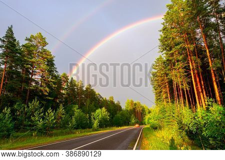 Idyllic Landscape With Double Rainbow After Rain. Road After Storm And Rain.