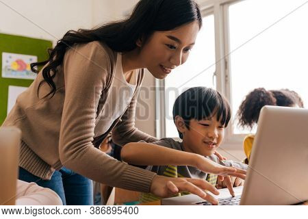 Young Adult Smiling Beautiful Asian Teacher Helping Elementary Student Boy With Laptop In Computer C