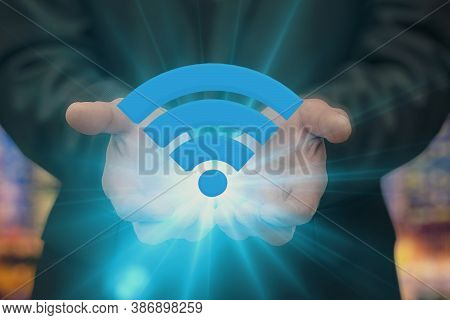 A Businessman Holds A Shining Wi-fi Icon Against The Background Of The Evening City. Concept: Free I