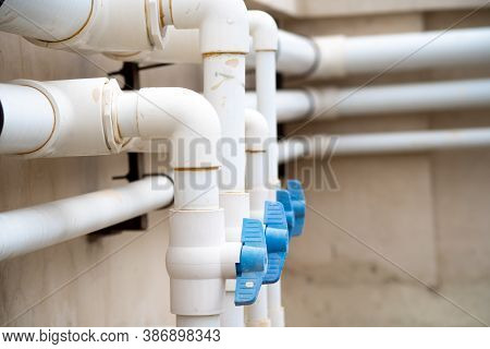White Pvc Pipes With Cool Blue Taps, Valves And Cocks That Stand Out Shot In A Home Office Maintenan