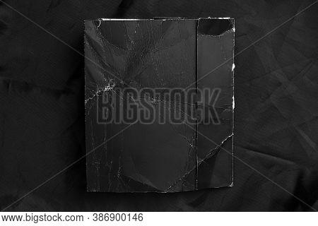 Black Wrinkled Paper With Frayed Folds On Black Wrinkled Synthetic Material. Close-up. Grunge Mock U