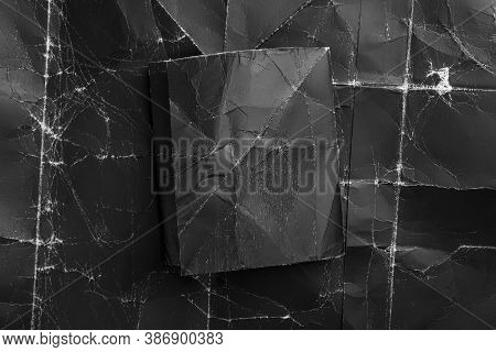 Black Wrinkled Old Paper Is Crumpled On Old Shabby Black Packaging Material Close-up. Dark Abstract