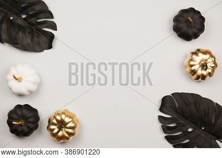 Trendy Halloween Frame With Golden Shiny Decorative Pumpkins. Flat Lay, Top View Trendy Holiday Conc