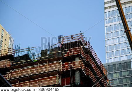 A Construction Worksite Building In A Big City Residential Skyscrapers With Blue Sky Behind