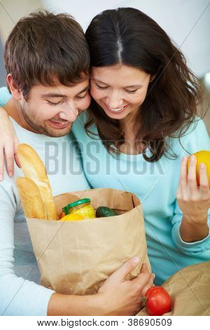 Young couple looking into paperbag with products with smiles