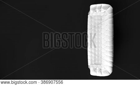 White Quilted Leather Sofa With Wooden Legs Isolated On Black Background View From Above. Template F