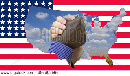 Close Up Photo Of A Handshake Between Afroamerican And European Hands Inside Of Us Map Silouette. Ha