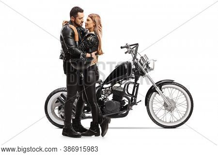 Full length shot of bikers man and woman in embrace in front of a chopper motorbike isolated on white background