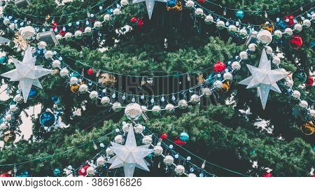 Close Up Of Big Christmas Tree With Different Christmas Toys And Decorative Adornments On Street. Co