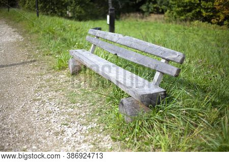Wooden Bench On The Street. A Place To Rest. An Unpainted Park Bench. Place For A Walk. A Shop On Th