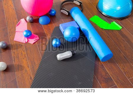 Aerobic Pilates stuff like mat balls roller magic ring rubber bands on wooden floor poster