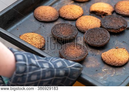 Burnt Cookies. A Hand In A Oven Glove, Potholder Picks Up A Black Baking Tray With Burnt Cookies