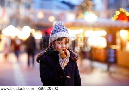 Cute Little Kid Girl Having Fun On Traditional Christmas Market During Strong Snowfall. Happy Child