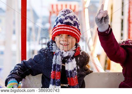 Two Little Kids, Boy And Girl Having Fun On Ferris Wheel On Traditional German Christmas Market Duri