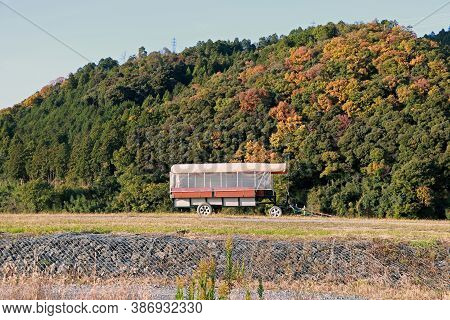 The Trailer On The Grassy Hill And Background Mountain Range With Blue Sky. The Drawbar Trailer For