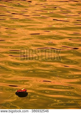Lamp Floating On The Golden Water Of River Ganges At Varanasi.