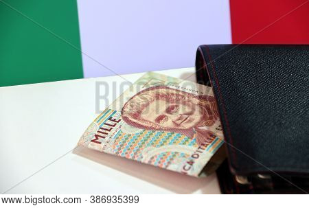 One Thousand Lire Of Italy Banknote With Black Wallet On The White Floor With Italia Flag Background