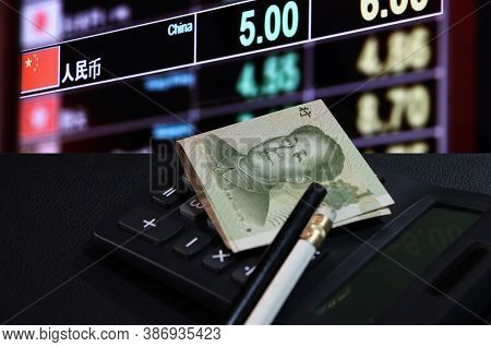 Yuan Banknote Of China With Pencil On Calculator On The Black Floor With Digital Board Of Currency E