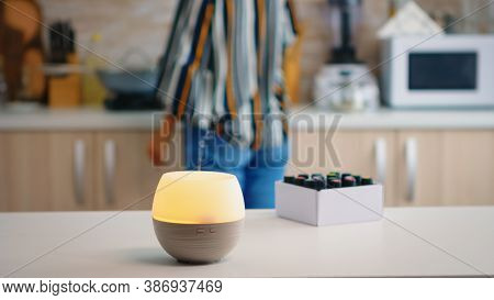 Woman In The Kitchen With Essential Oils Diffuser Working On The Table Top. Aroma Health Essence, We