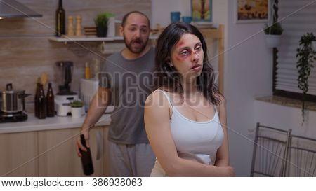 Alcoholic Man Screaming At Beaten Woman Walking Drunk Through The Kitchen. Traumatised Abused Terrif