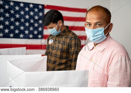People With Mask Busy At Polling Booth For Voting With Us Flag As Background - Concept Of In Person