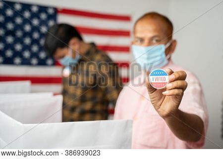 Man In Medical Mask Showing I Voted Sticker At Polling Booth With Us Flag As Background - Concept In