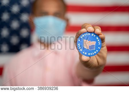 Man In Medical Mask Showing I Voted By Mail Sticker With Us Flag As Background - Concept Of Mail In