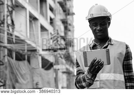 Young Happy Black African Man Construction Worker Smiling While Using Digital Tablet At Building Sit