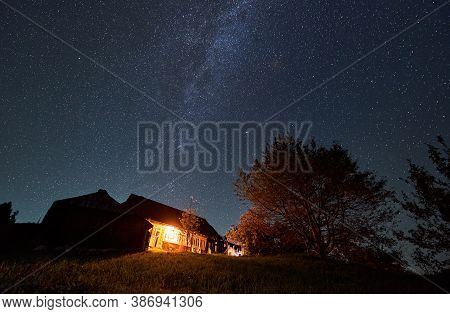 Horizontal Snapshot Of A Summerhouse In The Mountains Surrounded By Trees By Night, Amazing Starry N