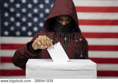 Man In Hoodie With Face Covered Casting Vote At Polling Booth With Us Falg As Background - Concept O