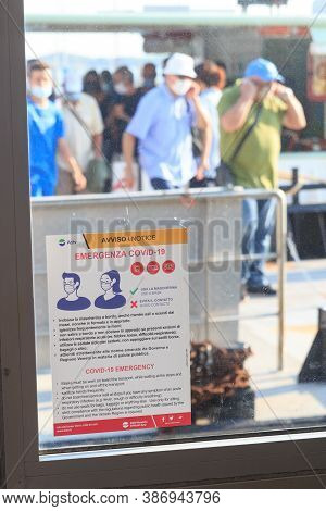 Venice, Italy - August 10, 2020: Coronavirus Warning Sign And People Wearing Masks At Actv Vaporetto