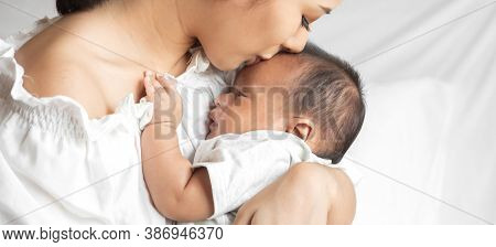 Portrait Of Enjoy Happy Love Family Asian Mother Playing With Adorable Little Asian Baby.mom Kiss Wi