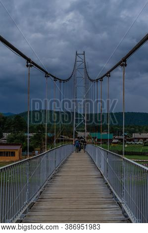Suspended Pedestrian Bridge With Metal Vertical Cables And Wooden Path Against The Background Of Vil