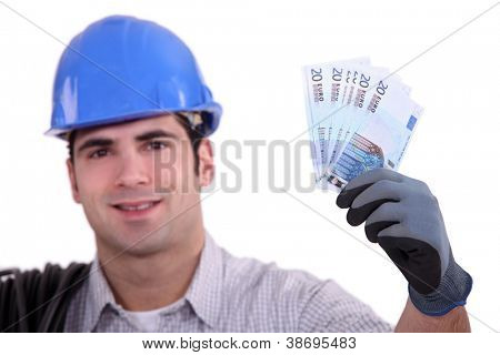 Construction worker holding up money