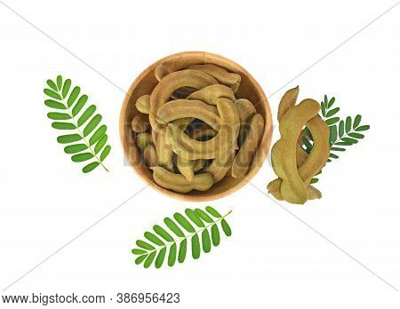 Top View 0f Young Tamarind In Wooden Bowl And Tamarind Leaf Isolated On White Background