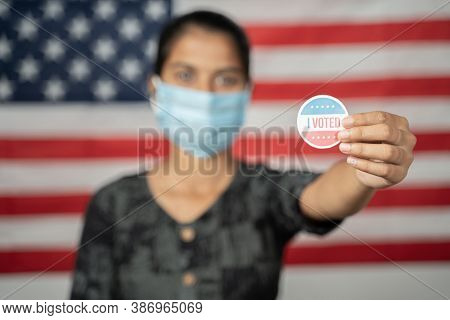 Girl With Mask Showing I Voted Sticker With Us Flag As Background - Concept Of Voting During Us Elec