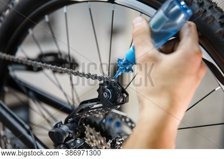 Bicycle assembly in workshop, man oiling the chain